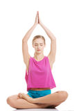 Beautiful young caucasian woman is exercising, doing yoga. Royalty Free Stock Photography