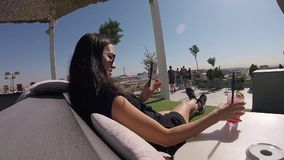 Beautiful woman filming her hand with cocktail on smartphone open air roof bar