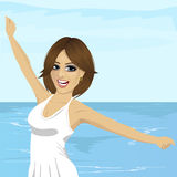 Beautiful young caucasian woman with her hands raised at beach Royalty Free Stock Images