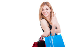 Beautiful young caucasian woman holding colored shopping bags. And showing peace or victory sign with copy space Stock Images