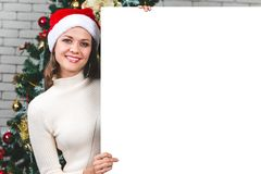 Beautiful and young caucasian woman holding and pointing to blank white board in front of big christmas tree. Concept for royalty free stock photography