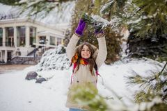 Beautiful young Caucasian woman joy happiness smile play with snow near a coniferous tree in a snowy park stock photos