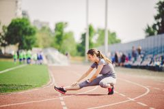 Beautiful young caucasian woman with long hair in tail and big breasts doing exercises, warming up and warming up muscles before t. Raining in running stadium stock photography