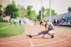 Beautiful young caucasian woman with long hair in tail and big breasts doing exercises, warming up and warming up muscles before t. Raining in running stadium royalty free stock image