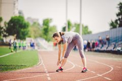 Beautiful young caucasian woman with long hair in tail and big breasts doing exercises, warming up and warming up muscles before t. Raining in running stadium royalty free stock images