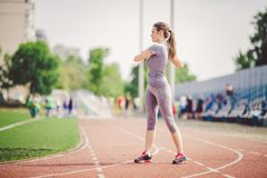 Beautiful young caucasian woman with long hair in tail and big breasts doing exercises, warming up and warming up muscles before t. Raining in running stadium royalty free stock photo