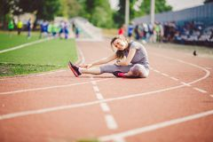 Beautiful young caucasian woman with long hair in tail and big breasts doing exercises, warming up and warming up muscles before t. Raining in running stadium royalty free stock photos