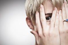 Beautiful Young Caucasian Woman Peeking Through Fingers Stock Photography