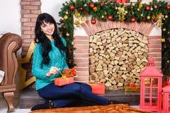 Beautiful young caucasian woman sitting near a decorative firepl Stock Images