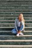 Beautiful young blonde woman smiling on urban steps. Royalty Free Stock Photography