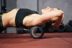 Beautiful young caucasian woman sportswoman uses a foam roller massager for relaxation, stretching muscles and back pain. Girl in royalty free stock photo