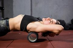 Beautiful young caucasian woman sportswoman uses a foam roller massager for relaxation, stretching muscles and back pain. Girl in stock images