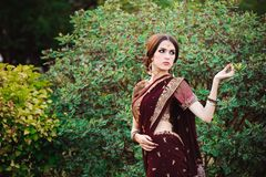 Beautiful young caucasian woman in traditional indian clothing sari with bridal makeup and jewelry and henna tattoo on. Hands royalty free stock photo