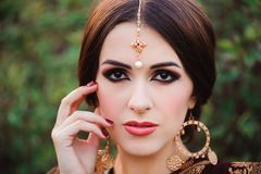 Beautiful young caucasian woman in traditional indian clothing sari with bridal makeup and jewelry and henna tattoo on. Hands royalty free stock image