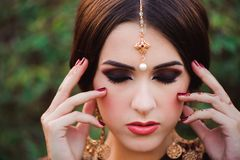 Beautiful young caucasian woman in traditional indian clothing sari with bridal makeup and jewelry and henna tattoo on. Hands stock photography