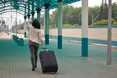Beautiful young Caucasian woman traveling pulling a luggage at the station, summer, vacation Royalty Free Stock Photography