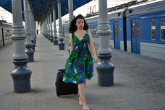 Beautiful young Caucasian woman traveling pulling a luggage at the station, summer, vacation Stock Photos