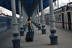 Beautiful young Caucasian woman traveling pulling a luggage at the station, summer, vacation Royalty Free Stock Image