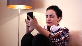 Beautiful young caucasian woman using an application on a smartphone and texting on a mobile phone. Beautiful young caucasian woman sitting with headphones stock footage