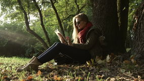 Beautiful young caucasian women using tablet in the park. Season, technology and people concept - young woman with tablet pc computer in autumn park stock video