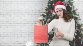 A beautiful young caucasion woman holding red shopping bag and t stock photo