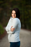 Beautiful young cheerful caucasian woman with dark brown hair. Beautiful young cheerful caucasian woman with brown hair walking in park on a cold autumn day stock images