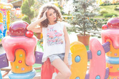 Beautiful young cheerful girl with curly hair in denim shorts and white T-shirt at an amusement park at sunset bright sun Royalty Free Stock Photography
