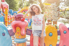 Beautiful young cheerful girl with curly hair in denim shorts and white T-shirt at an amusement park at sunset bright sun Royalty Free Stock Images