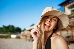 Beautiful young cheerful girl in funny hat rests at morning beach Stock Photos