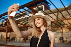 Beautiful young cheerful girl in hat rests at morning beach and makes selfie Stock Image