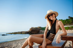 Beautiful young cheerful girl in hat and sunglasses rests at morning beach Royalty Free Stock Photography