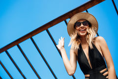 Beautiful young cheerful girl in hat and sunglasses rests at morning beach Royalty Free Stock Photos