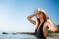 Beautiful young cheerful girl in hat and sunglasses rests at morning beach Stock Photos
