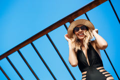 Beautiful young cheerful girl in hat and sunglasses rests at morning beach Stock Photo