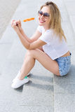 Beautiful young cheerful happy girl eating ice cream , smiling in shorts and a white T-shirt on the area on a bright sunny day Royalty Free Stock Images