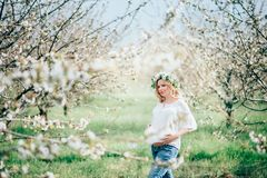 Beautiful young cheerful pregnant woman in wreath of flowers on head touching belly while walking in spring tree garden. Beauty Royalty Free Stock Image