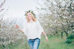 Beautiful young cheerful pregnant woman in wreath of flowers on head touching belly while walking in spring tree garden. Beauty Stock Images