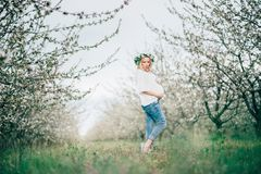 Beautiful young cheerful pregnant woman in wreath of flowers on head touching belly while walking in spring tree garden. Beauty Stock Image