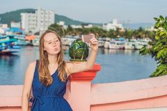 Beautiful young cheerful woman taking a selfie against the background of the sea and Vietnamese boats stock photography