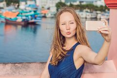 Beautiful young cheerful woman taking a selfie against the background of the sea and Vietnamese boats stock image