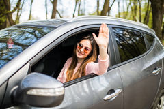 Beautiful young cheerful women looking at camera with smile and waving while sitting in her car Stock Photography