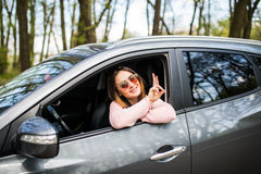 Beautiful young cheerful women looking at camera with smile and waving while sitting in her car Royalty Free Stock Photos