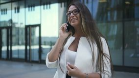 Beautiful young chief banker woman is talking on phone standing on background of office building. stock video