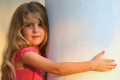 Beautiful young child on white column Stock Images