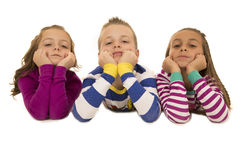 Beautiful young children wearing pajamas leaning on their elbows royalty free stock image