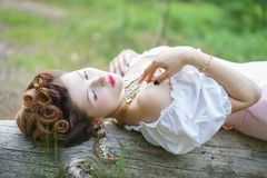 Beautiful young chubby girl posing in medieval retro corset and white vintage lingerie in the forest stock image