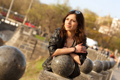 Beautiful young city woman. Portrait of a beautiful young girl near the ball stone in the city park Royalty Free Stock Photos