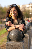 Beautiful young city woman. Portrait of a beautiful young girl near the ball stone in the city park Stock Photo