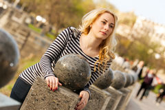 Beautiful young city woman. Portrait of a beautiful young girl near the ball stone in the city park Stock Image