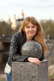 Beautiful young city woman. Portrait of a beautiful young girl near the ball stone in the city park Stock Photos